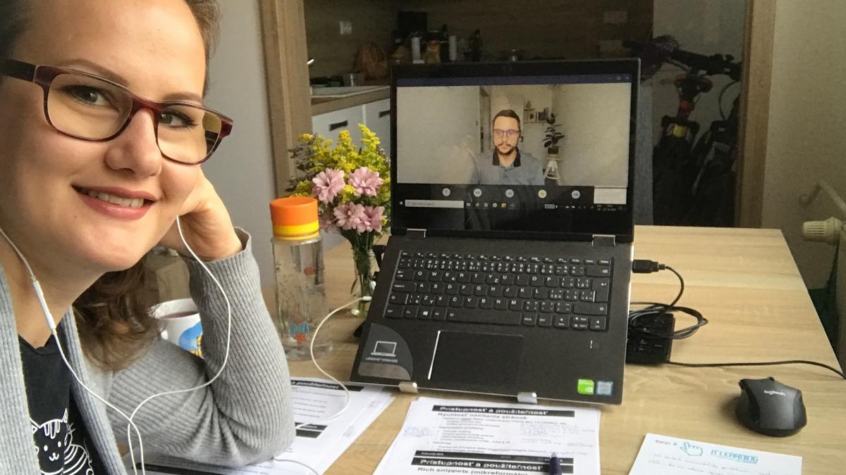 Testerka urzu vedľa počítača s lektorom kurzu na obrazovke