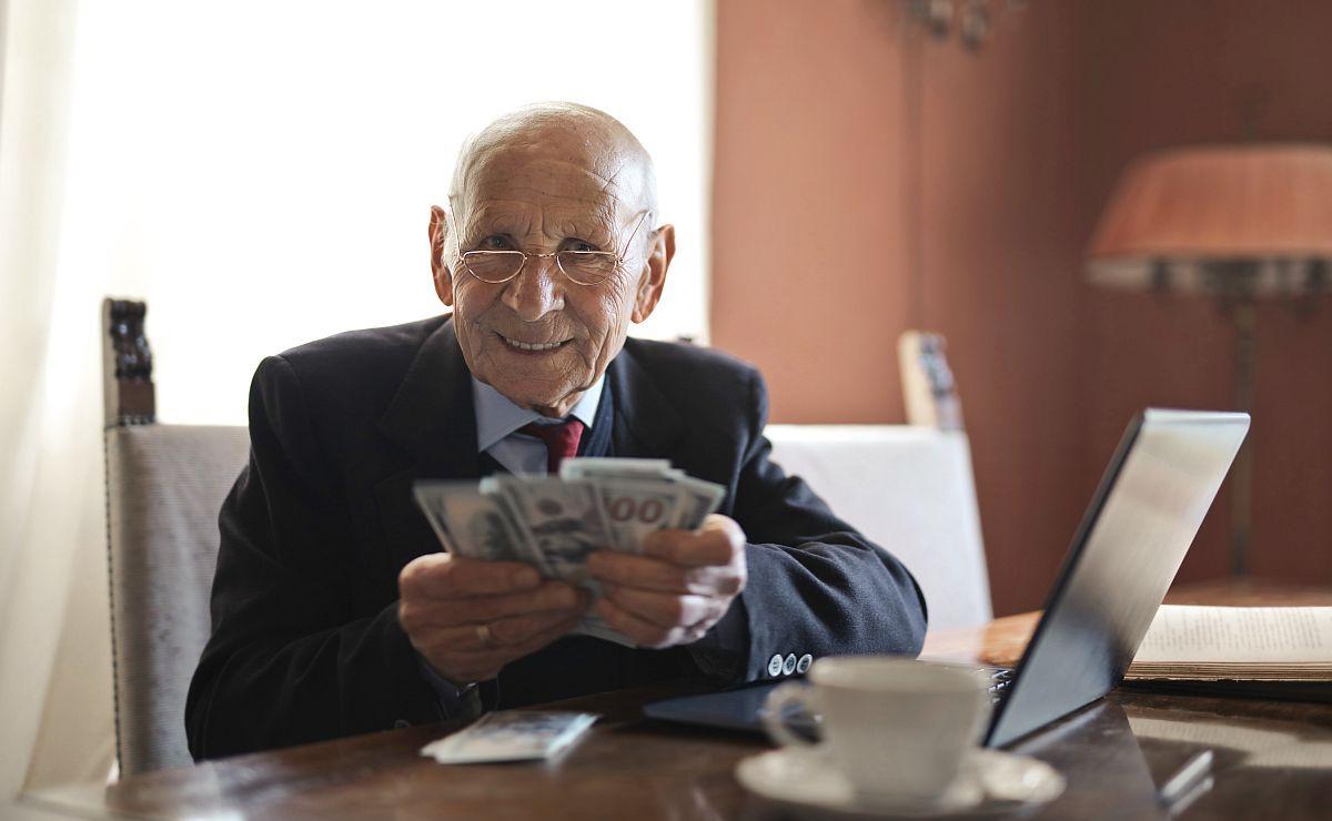 úspešný starší človek za stolom s notebookom ukazuje časť svojich peňazí